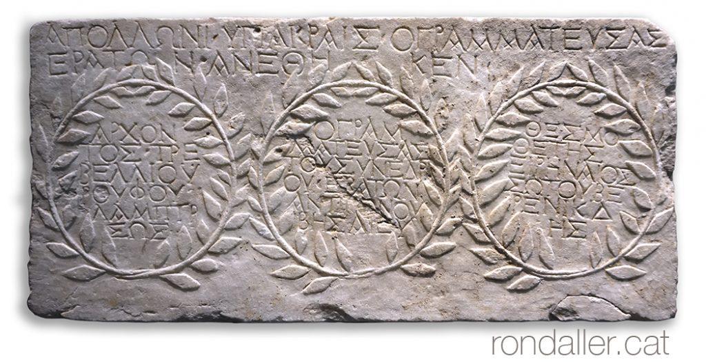 Llosa amb inscripcions i corones de llorer en relleu al Museu de l'Acròpoli.