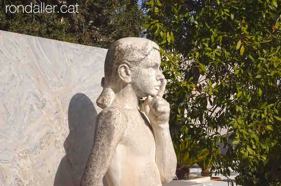 Escultura funerària d'una nena amb el dit a la boca en senyal de silenci.